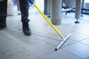 Dry mopping the floor before using floor scrubber.